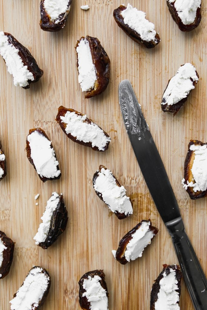 closeup overhead photo of medjool dates sliced in half and stuffed with goat cheese