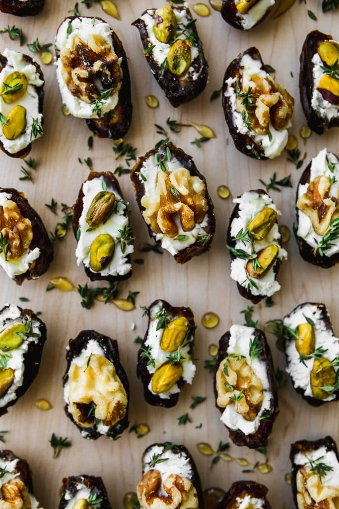 closeup photo of multiple dates cut in half, stuffed with goat cheese, and topped with walnuts, pistachios, honey, and fresh thyme