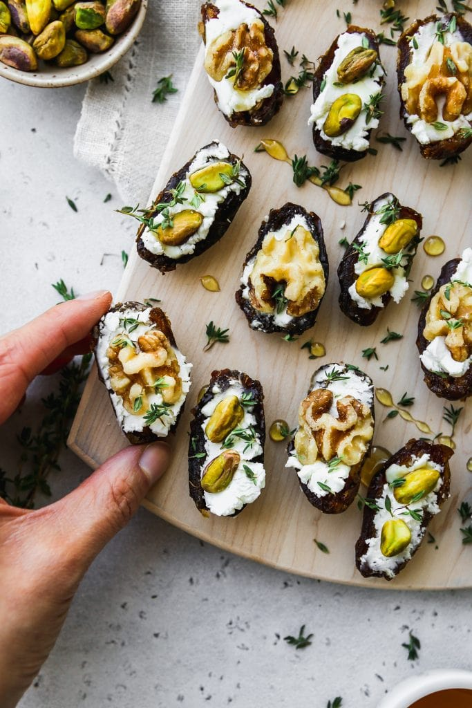 overhead photo of hand grabbing one of 12 medjool dates stuffed with goat cheese and topped with walnuts, pistachios, honey, and thyme on a wood cutting board