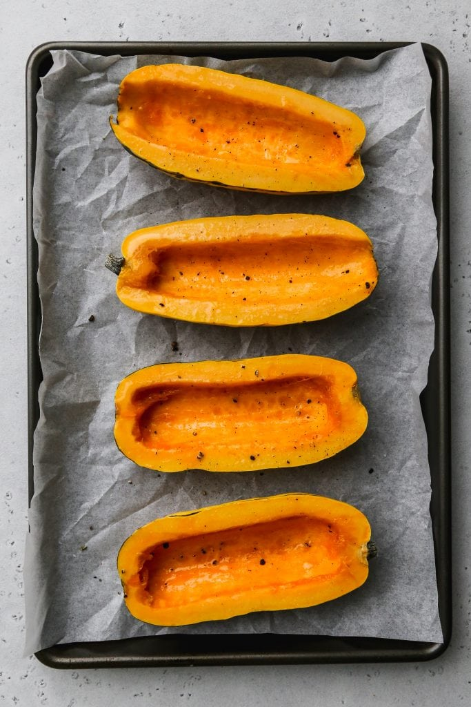 overhead photo of baking sheet topped with 4 uncooked halves of delicata squash