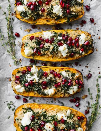 overhead photo of 4 halves of delicata squash stuffed with kale and quinoa and topped with goat cheese, pomegranates, and thyme on white parchment paper