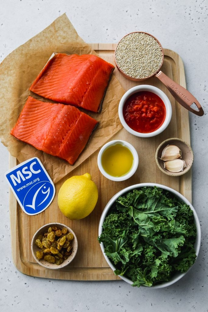overhead photo of wood cutting board with ingredients for cooking a salmon recipe on top