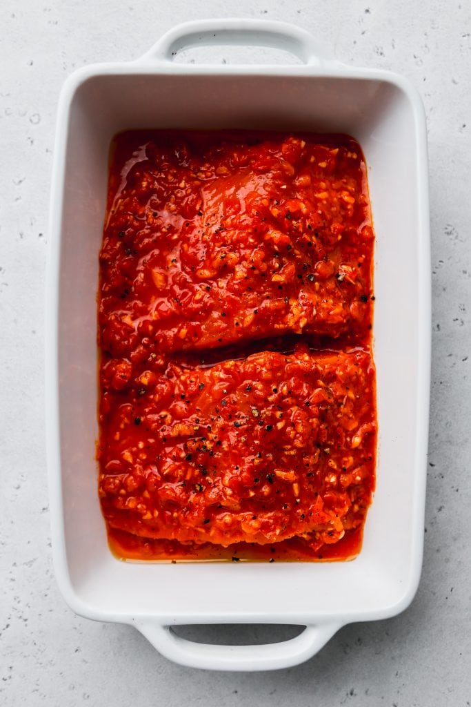 overhead photo of white baking dish with two salmon fillets topped with a harissa sauce on top