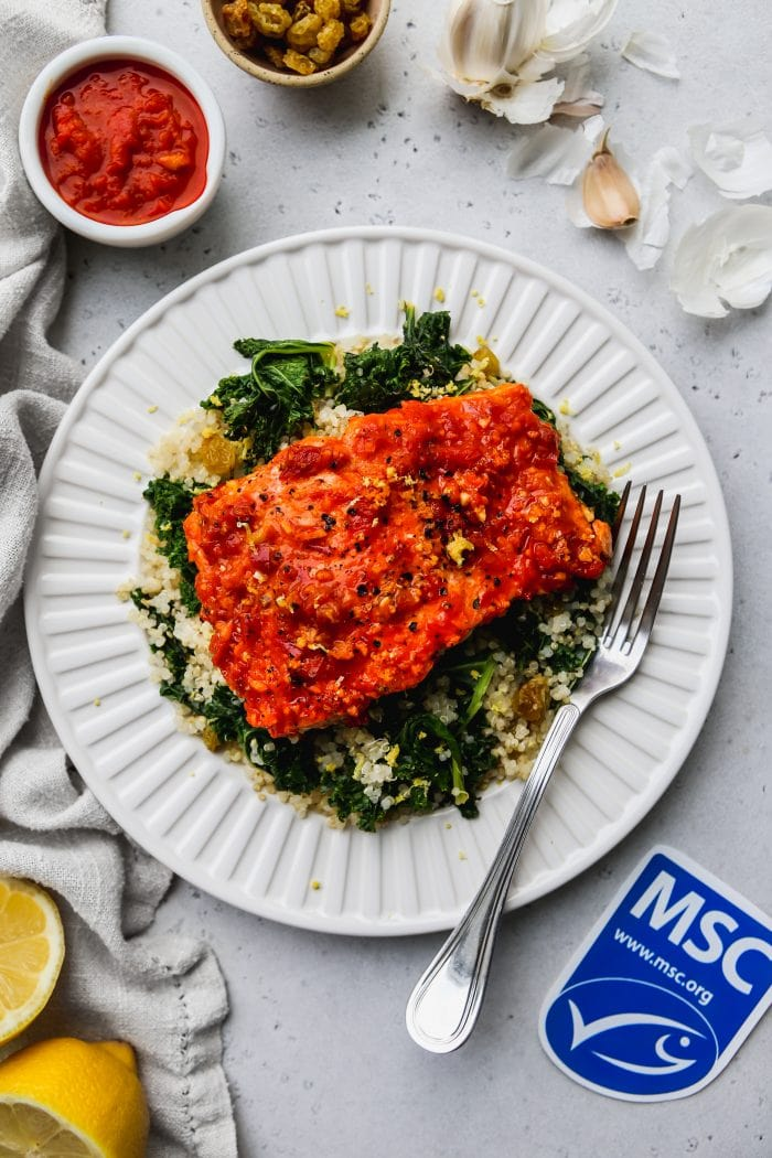 overhead photo of baked harissa salmon over lemon kale quinoa on a white plate. Ingredients garnish the outside of the plate, along with a MSC blue label