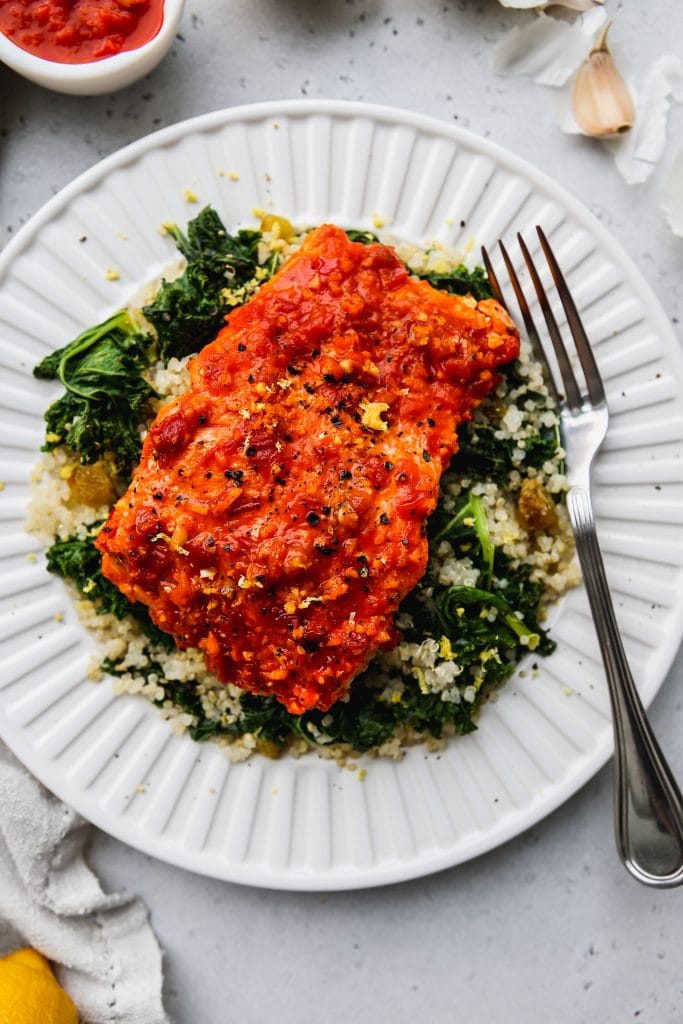 closeup overhead photo of baked harissa salmon over lemon kale quinoa on a white plate
