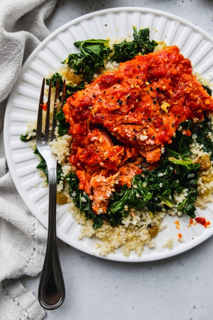 closeup overhead photo of a partially-eaten baked harissa salmon over lemon kale quinoa on a white plate