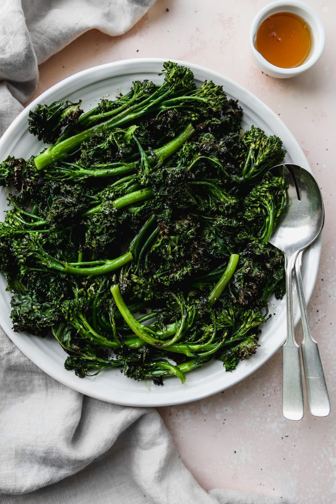 overhead photo of roasted broccolini and kale on a white serving platter with small bowl of honey and silver serving utensils