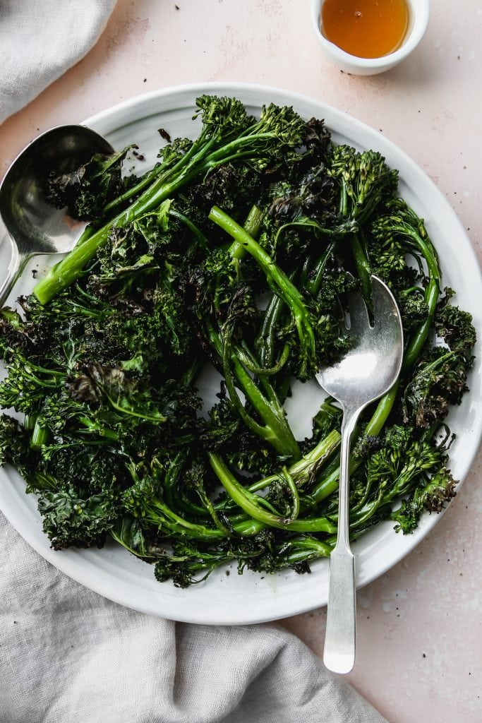 overhead photo of roasted broccolini and kale on a white serving plate with silver utensils