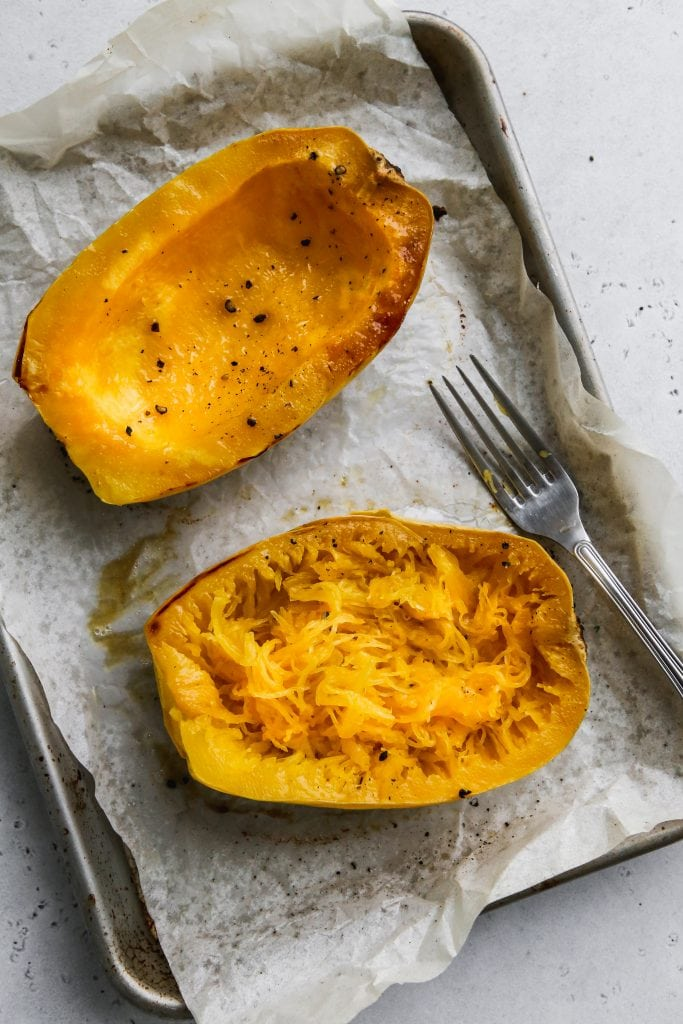 overhead photo of roasted spaghetti squash facing up with inside scraped out on a baking sheet