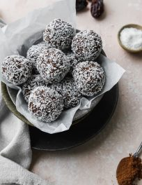 overhead photo of a bowl of chocolate coconut date balls on a light pink backdrops