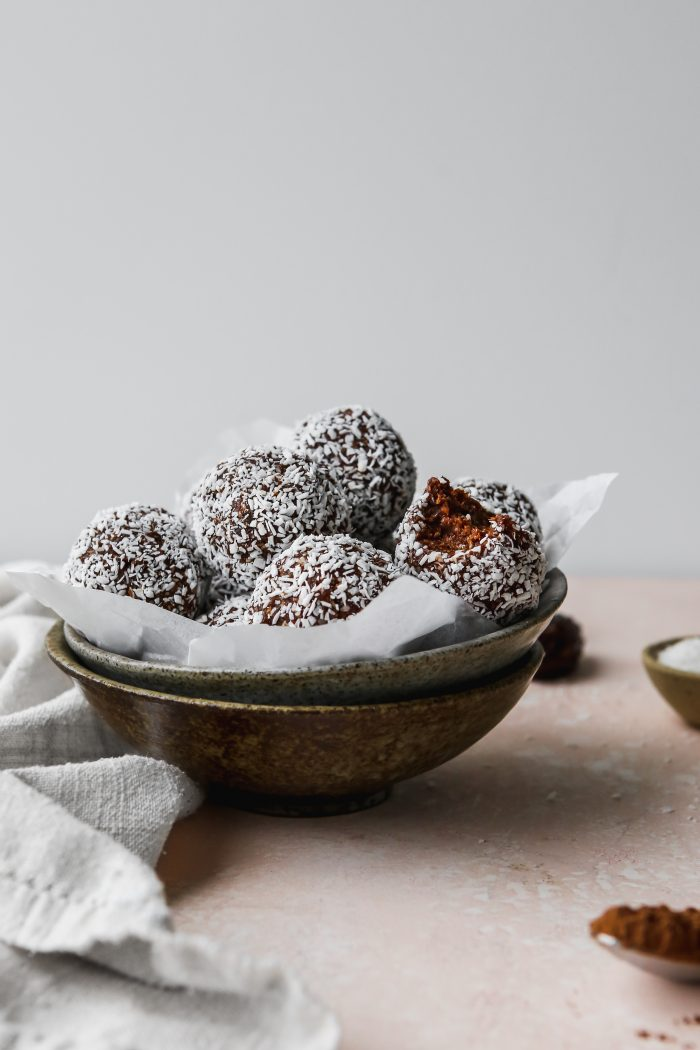 straight on photo of a parchment-lined bowl filled with chocolate coconut date balls