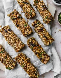 overhead photo of 8 homemade no-bake trail mix granola bars on a wood cutting board with white parchment on top