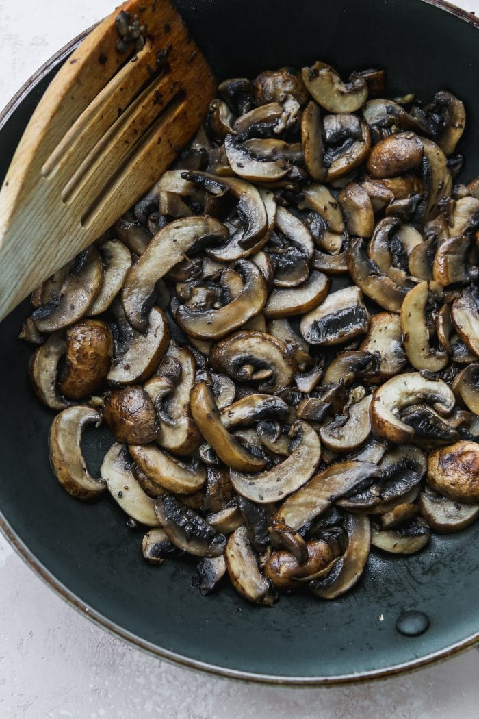 overhead photo of a dark skillet with sauteed cremini mushrooms inside