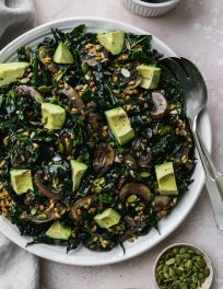 overhead photo of large white serving plate topped with warm mushroom, kale, and farro salad with avocado chunks on top