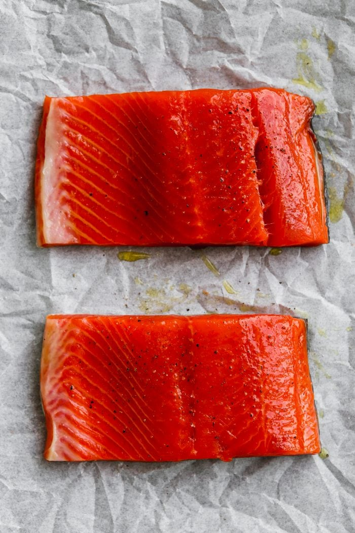 Overhead photo of two pieces of salmon on white parchment paper.
