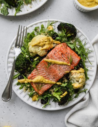 Overhead photo of a white plate topped with arugula, cauliflower, broccoli, salmon, and a drizzle of curry tahini dressing.