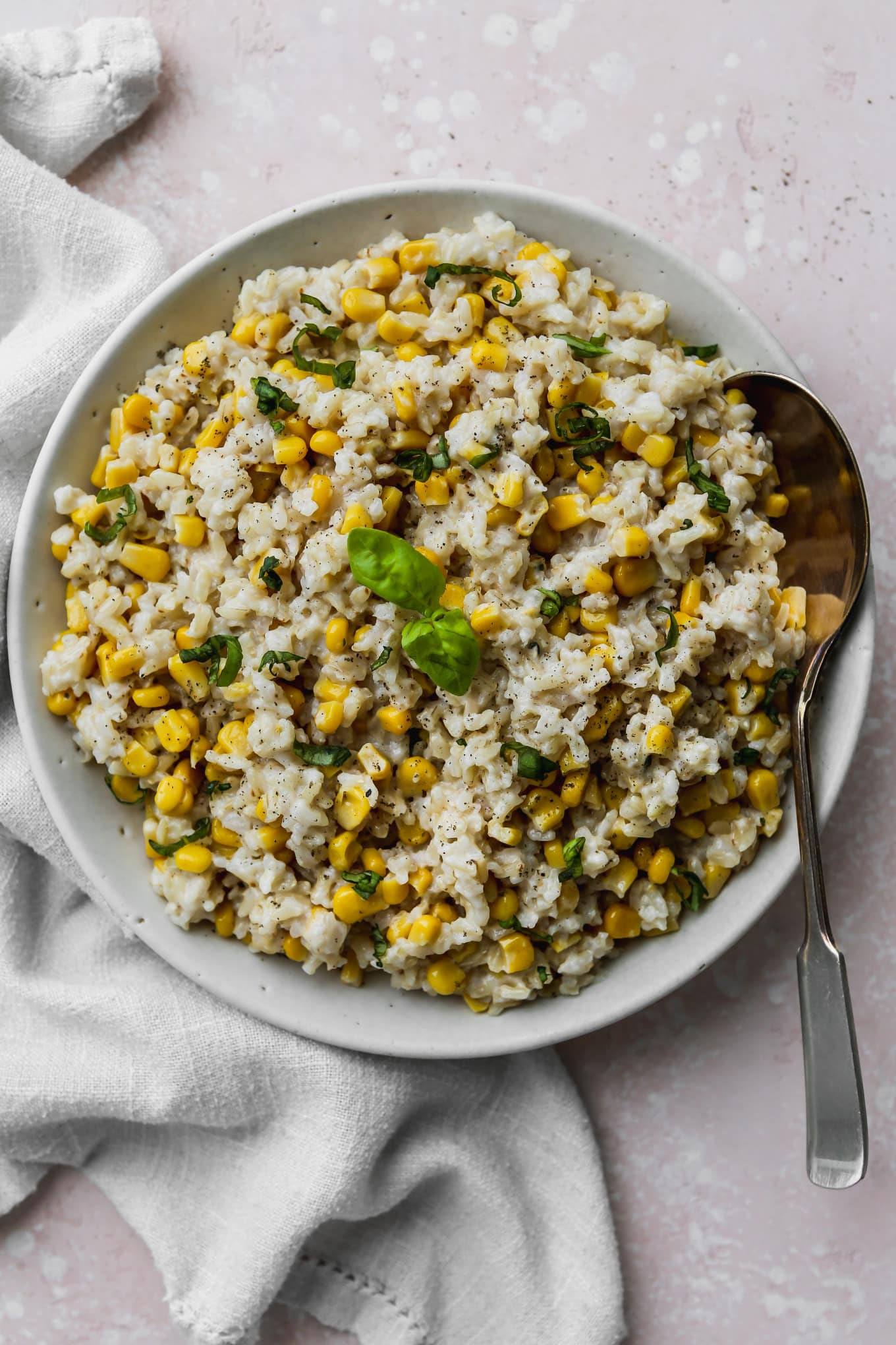 Overhead photo of cooked coconut corn rice in a large white bowl.