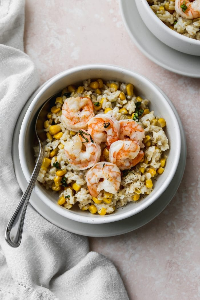 Overhead photo of a small white bowl with a serving of coconut corn rice topped with sautéed shrimp.