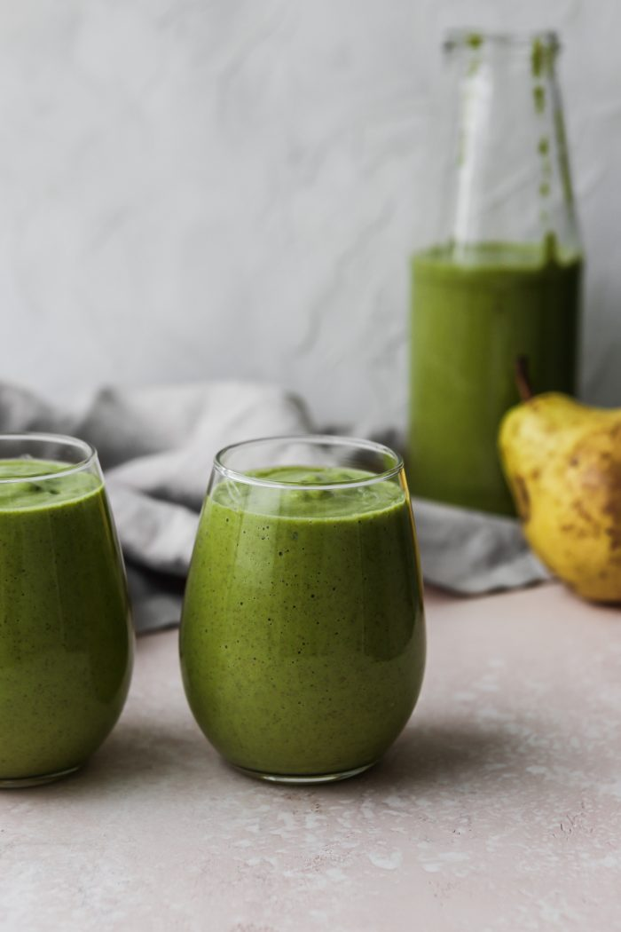 Straight on photo of two small glasses filled with a green smoothie, with a large glass jar and pear in the background.