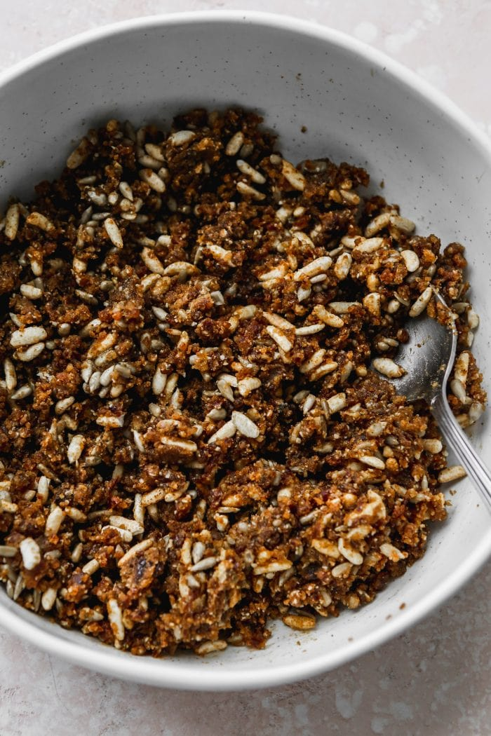 An overhead photo of a large white bowl filled with a mixture of dates, peanut butter, rice crispies, and seeds.