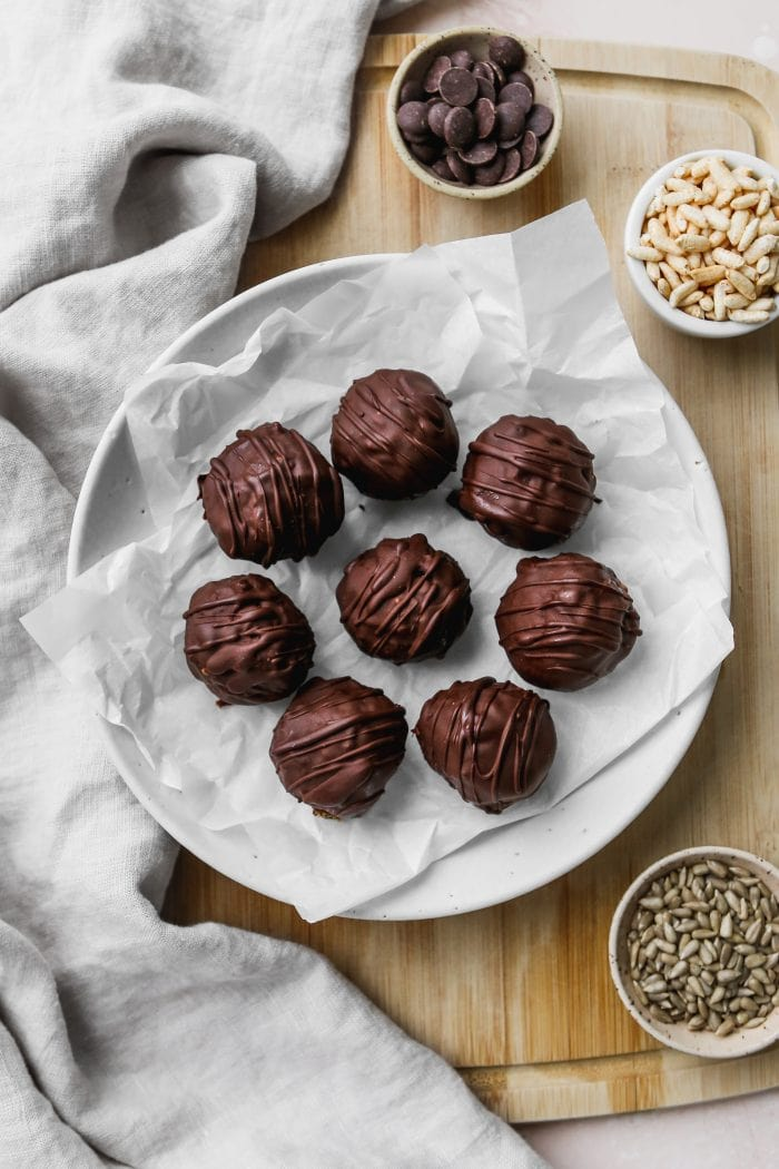 Overhead photo of 8 chocolate covered energy balls on top of a white plate and wooden cutting board.