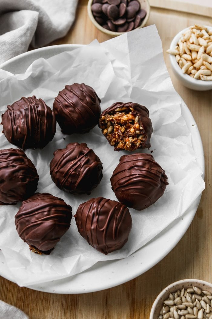 Closeup overhead photo of 8 chocolate covered peanut butter rice crispy balls on top of a white plate and wooden cutting board.