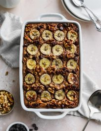 Overhead photo of a white baking dish filled with a peanut butter banana baked oatmeal.