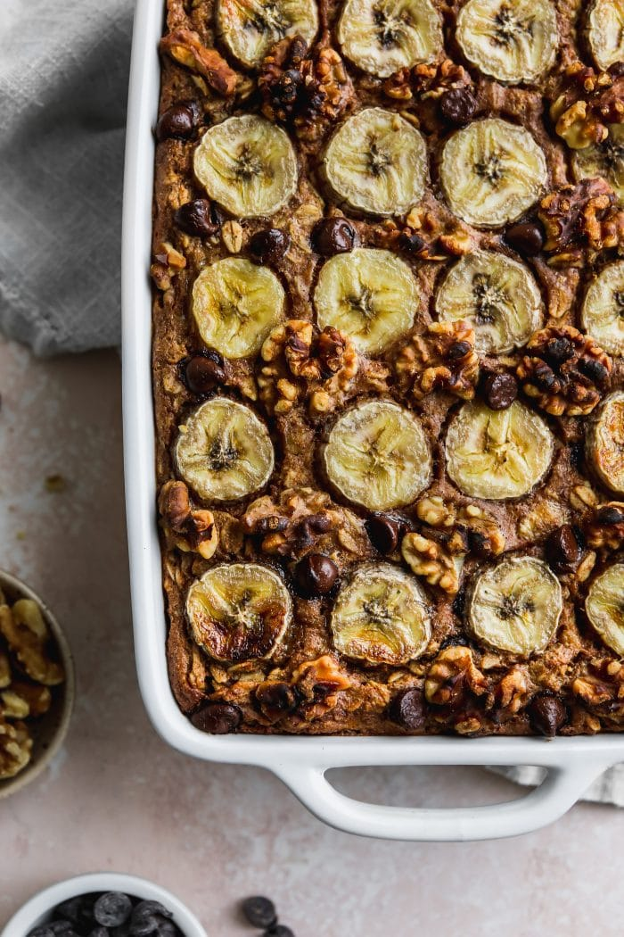 Closeup overhead photo of a white baking dish filled with a peanut butter banana baked oatmeal.