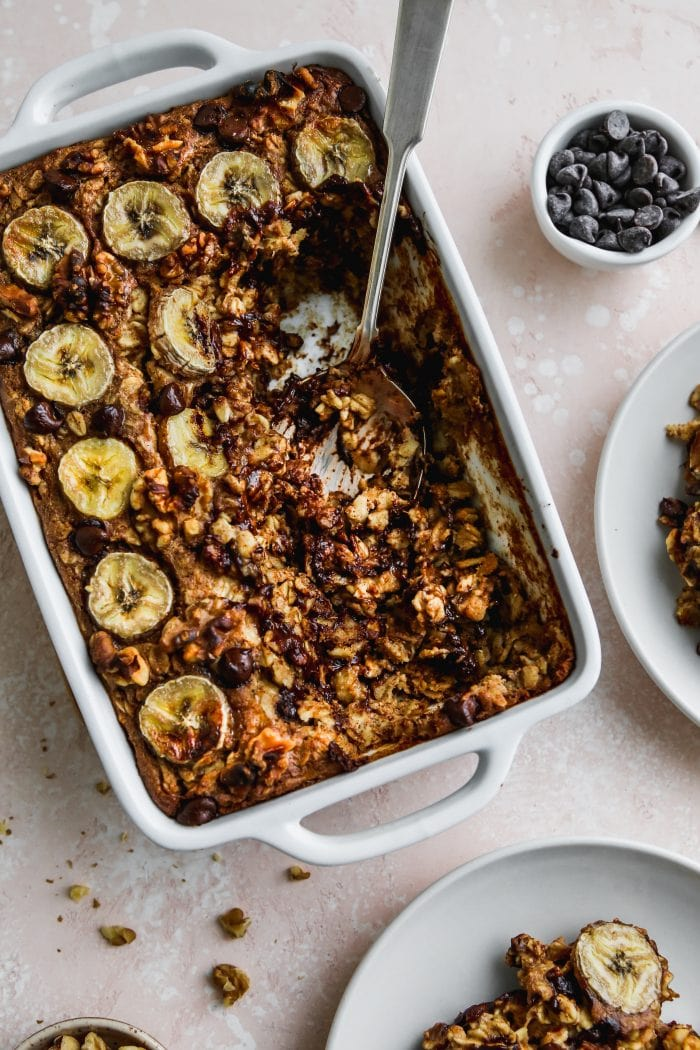 Overhead photo of a white baking dish with a half-served banana baked oatmeal inside.