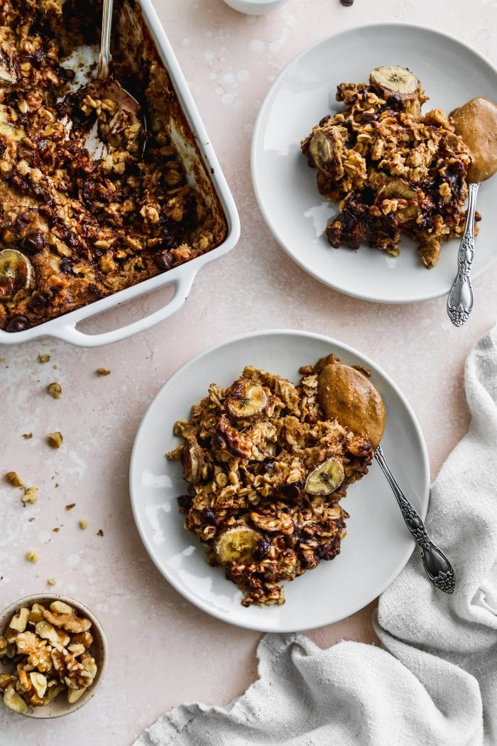 Overhead photo of two white plates topped with servings of banana baked oatmeal and a scoop of peanut butter in a spoon.