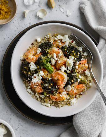Overhead photo of white bowl filled with quinoa, sautéed shrimp, broccoli, feta, and lemon zest.