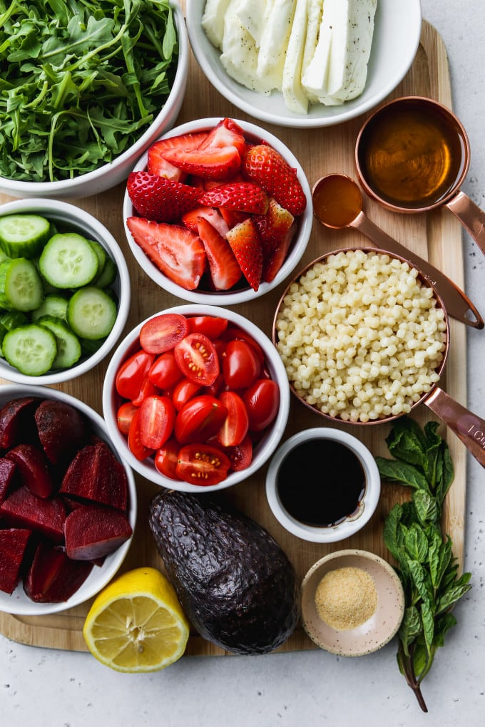 Overhead photo of small bowls filled with salad ingredients on top of a wooden cutting board.