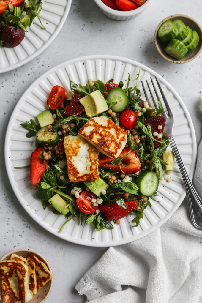 Overhead photo of a white plate topped with an arugula, halloumi, couscous, and vegetable salad.