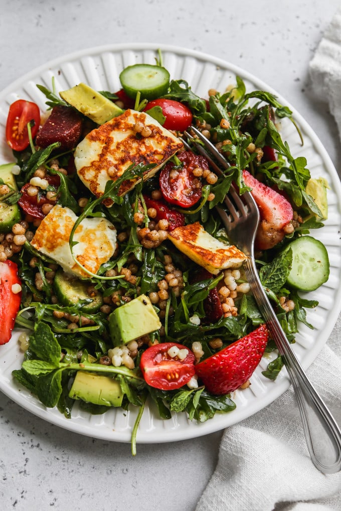 Closeup photo of a halloumi, arugula, couscous, and veggie salad tossed together on a white plate.
