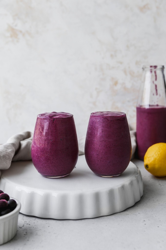 Straight on photo of two small glasses filled with blueberry lemon avocado smoothie on a white stand.