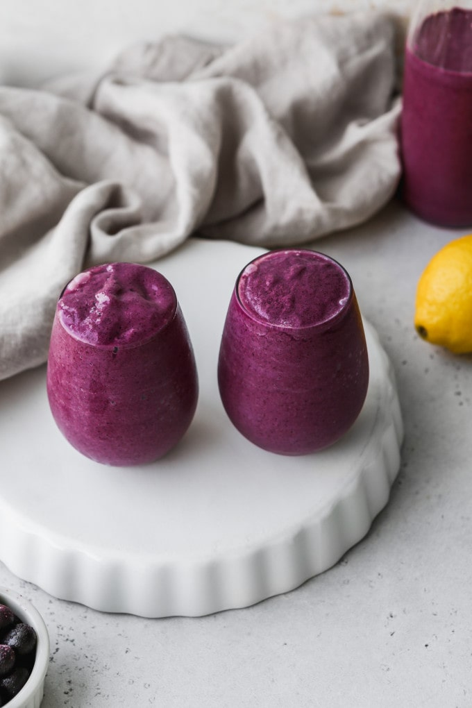 Overhead photo of two small glasses filled with blueberry lemon avocado smoothie on a white stand.