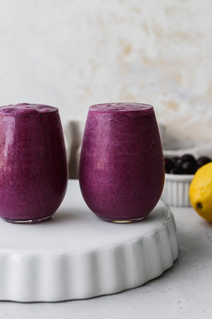 Straight on closeup photo of two small glasses filled with blueberry lemon avocado smoothie on a white stand.