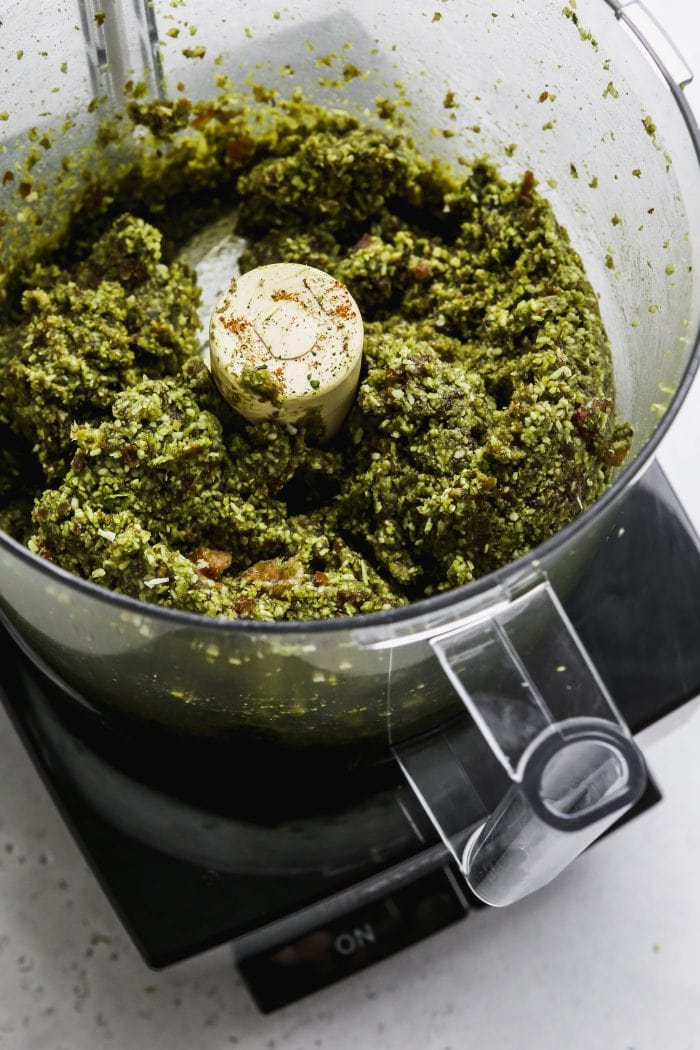 Overhead photo of a large food processor with mixed energy ball filling inside.