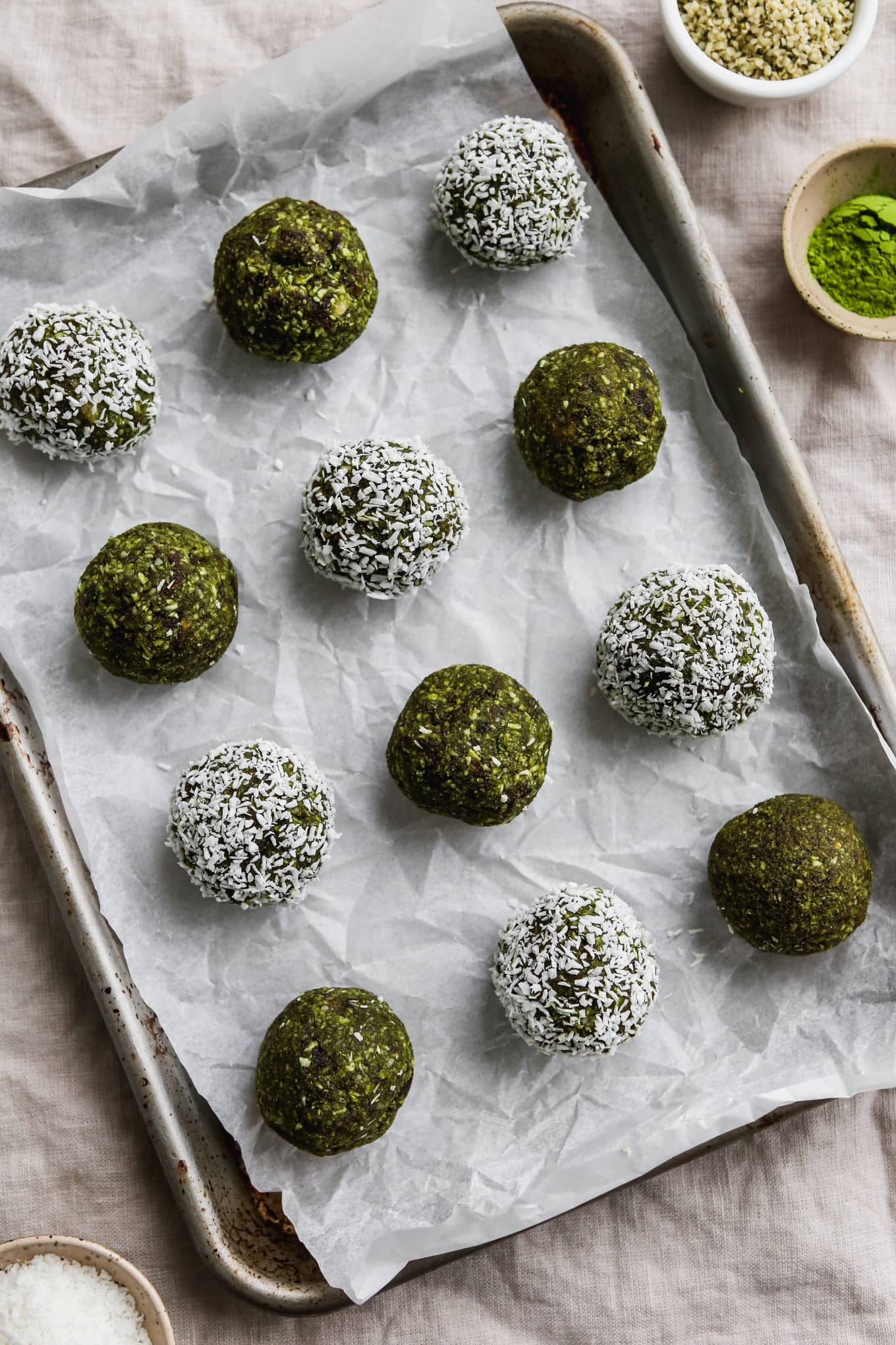 Overhead photo of 12 matcha energy balls on top of a parchment lined baking sheet.