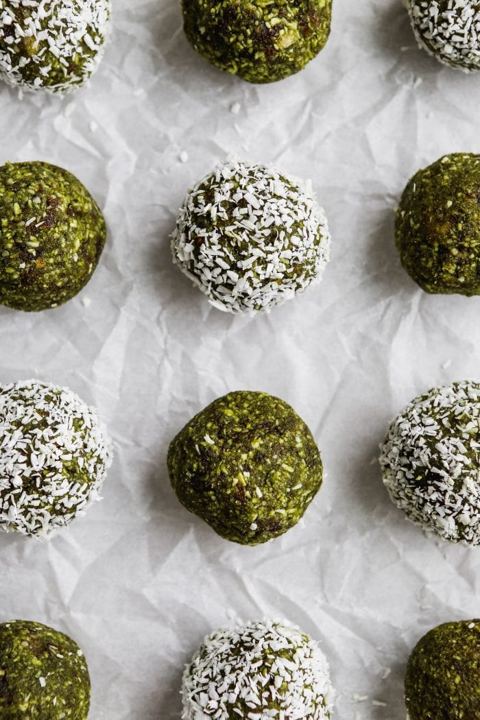Closeup overhead photo of 12 matcha energy balls on a piece of white parchment paper.