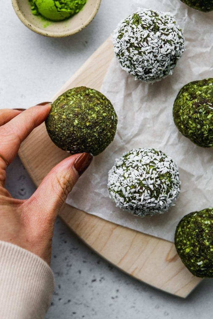 Closeup shot of a hand grabbing one matcha energy ball off of a wooden cutting board.