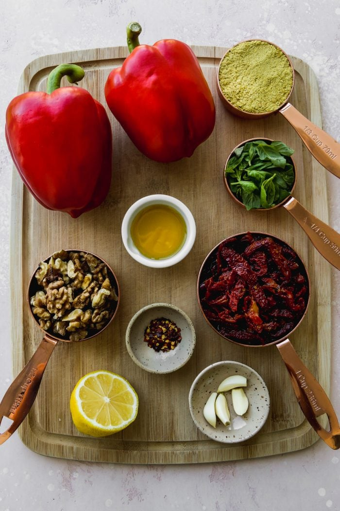 Overhead photo of small bowls and cups of ingredients on a wooden cutting board.