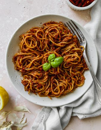 Overhead photo of a white bowl filled with red pesto spaghetti.