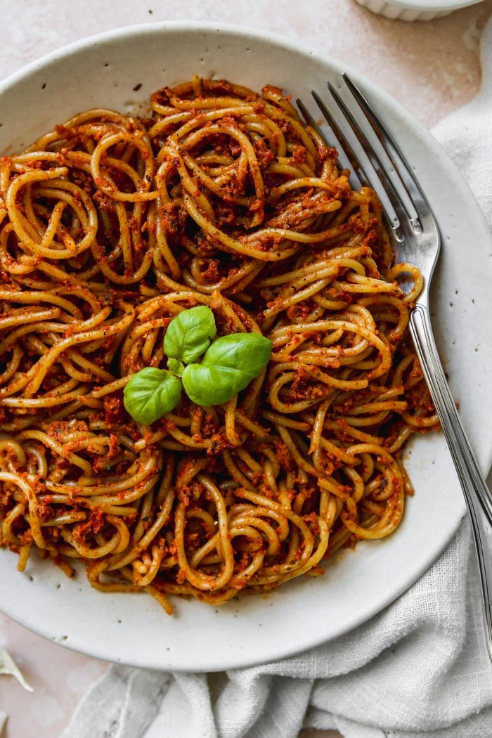 Closeup photo of a white bowl filled with red pesto spaghetti.