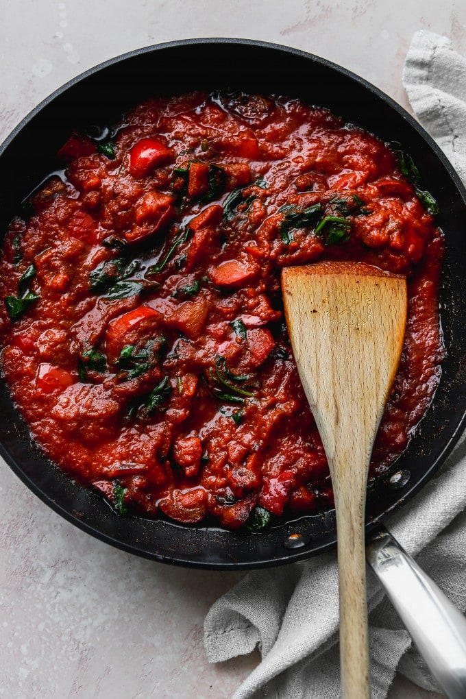 Overhead photo of a black skillet with cooked tomato sauce inside.