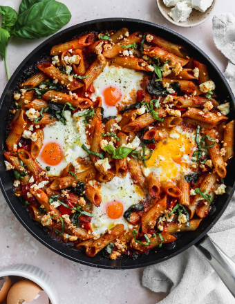 Overhead photo of a baked tomato pasta with eggs, feta, and basil in a black skillet.
