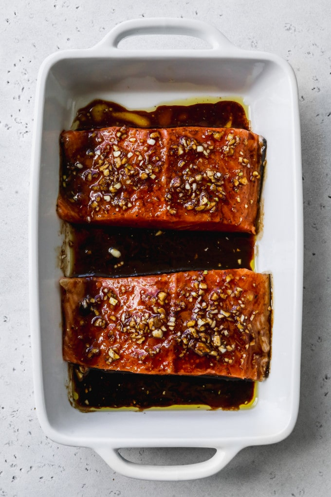 Overhead photo of two pieces of salmon and balsamic marinade in white baking dish.