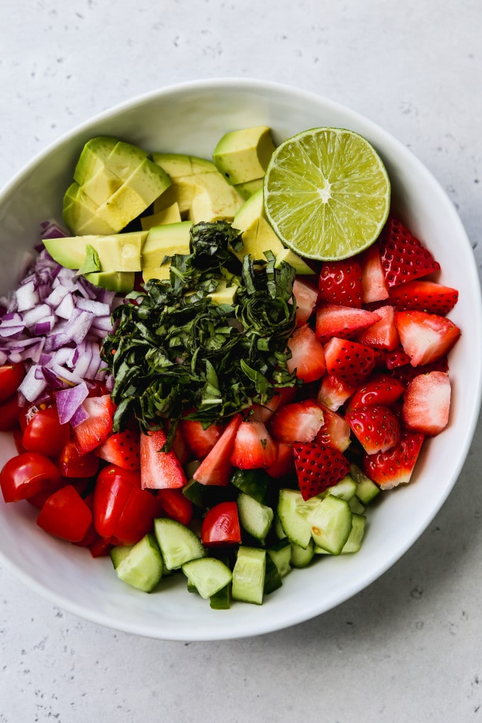 Overhead photo of a white bowl filled with chopped tomatoes, strawberries, avocados, cucumbers, onions, basil, and half a lime.