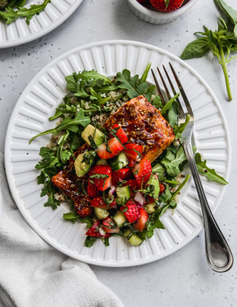 Overhead photo of a white plate topped with a balsamic baked salmon and strawberry basil salsa over arugula and quinoa.