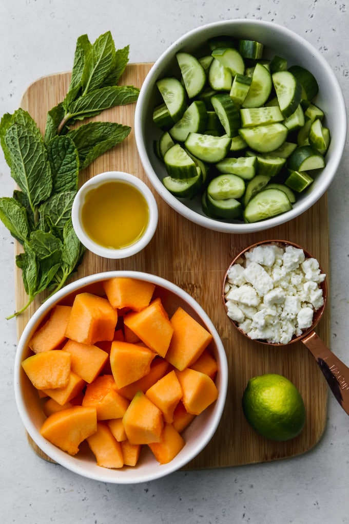 Overhead photo of bowls of salad ingredients on top of a wood cutting board.
